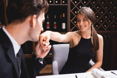 Selective focus of man in suit kissing hand of elegant girlfriend in restaurant stock vector