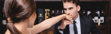 Panoramic crop of elegant man kissing hand of girlfriend in restaurant stock vector