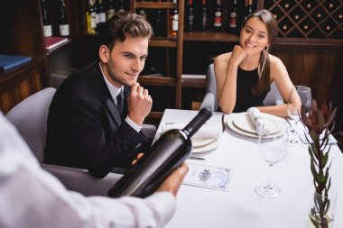 Selective focus of young couple looking at sommelier with bottle of wine in restaurant stock vector