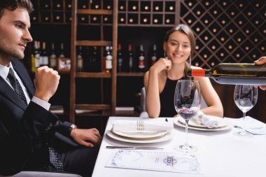 Selective focus of sommelier pouring wine in glass near elegant couple sitting at table in restaurant stock vector
