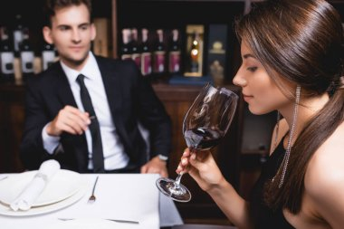 Selective focus of young woman holding glass of wine near boyfriend in restaurant stock vector