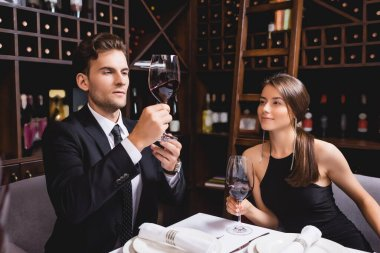 Young man in suit looking at glass of wine near girlfriend in restaurant stock vector