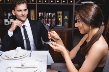 Selective focus of young woman looking at glass of wine near boyfriend in formal wear in restaurant stock vector