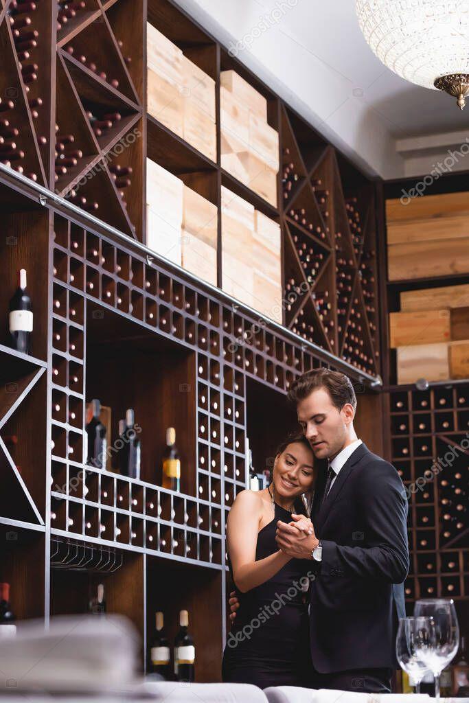 Selective focus of man in suit dancing with elegant girlfriends in restaurant stock vector