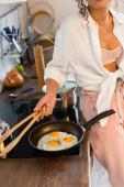 oříznutý pohled na ženu držící kuchyňské kleště u vajec na pánvi v kuchyni