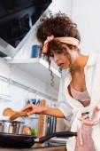 vystresovaná mladá žena drží kuchyňské kleště a při pohledu na pánev