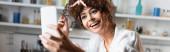 panoráma koncepció izgatott nő csinál szelfi okostelefon a konyhában
