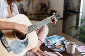 kivágott kilátás fiatal nő játszik akusztikus gitár otthon