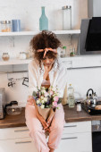 curly woman sitting on kitchen table and looking at flowers