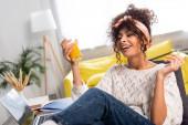 potěšená žena drží sklenici pomerančové šťávy poblíž notebooku na stole