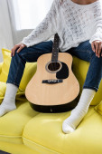 cropped view of woman sitting on sofa with acoustic guitar