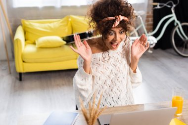 Selective focus of excited woman laughing and looking at laptop stock vector