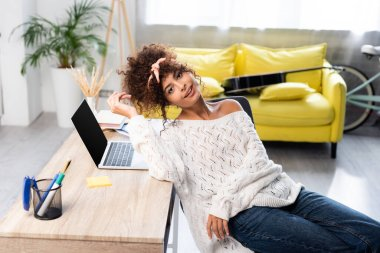 Joyful woman sitting near laptop with blank screen on desk stock vector