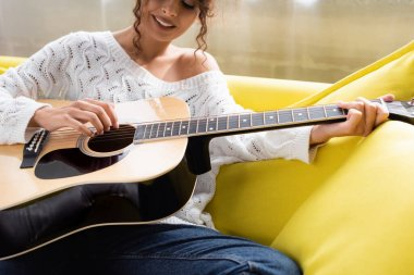 Cropped view of young curly woman playing acoustic guitar on sofa in living room stock vector