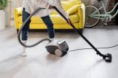 Teilansicht einer Frau in Socken mit Staubsauger beim Putzen zu Hause