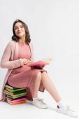 potěšená a těhotná žena sedí na knihách a dotýká břicho na bílém