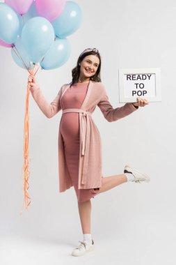 Neşeli ve hamile bir kadın elinde balonlarla beyaz harfleri patlatmaya hazır.