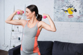 joyful pregnant woman exercising with pink dumbbells at home