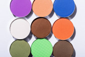 top view of multicolored eyeshadow on white background