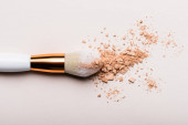 top view of cosmetic brush with face powder on beige background