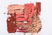 top view of pink, beige and brown abstract brushstrokes of lipstick and face powder on white background