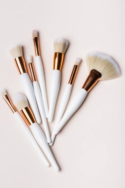 Top view of white and golden cosmetic brushes set on beige background stock vector