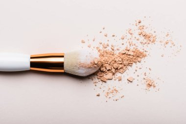 Top view of cosmetic brush with face powder on beige background stock vector