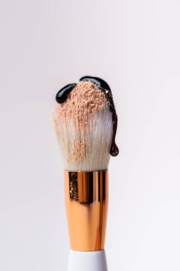 Close up view of cosmetic brush with face powder and dripping black liquid isolated on white stock vector