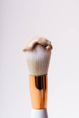 Close up view of cosmetic brush with face foundation isolated on white stock vector