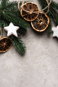 Top view of dried orange slices, cookies and pine branch on textured background