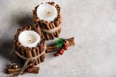Vonné svíčky zdobené skořicovými tyčinkami na šedém a texturovaném pozadí
