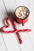 Piros csésze kakaó közel karácsonyi cukornád alakú szerelem szimbólum