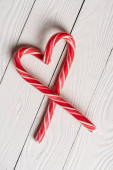 Top view of christmas candy canes in shape of love symbol on wooden background