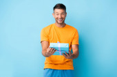 pleased man in t-shirt holding wrapped gift box on blue
