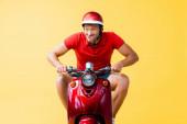 legrační muž v helmě na koni červený skútr a vyčnívat jazyk na žluté