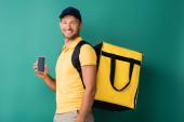 veselý doručovatel nesoucí žlutý batoh a držící smartphone s prázdnou obrazovkou na modré