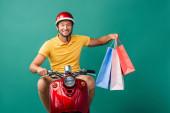 šťastný dodávka muž v helmě na koni skútr při držení nákupních tašek na modré