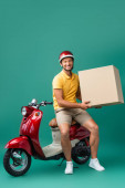 Photo cheerful delivery man in helmet holding big carton box near scooter on blue