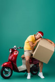 Photo tired delivery man in helmet holding big carton box near scooter on blue