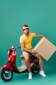 Photo exhausted delivery man in helmet holding big carton box near scooter on blue