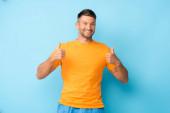 šťastný muž ve žlutém tričku ukazující palce nahoru na modré