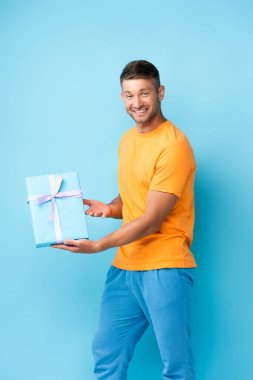 Cheerful man in t-shirt holding wrapped gift box on blue stock vector