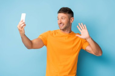 Man in t-shirt holding smartphone and taking selfie while waving hand on blue stock vector