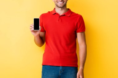 Cropped view of man holding smartphone with blank screen on yellow stock vector