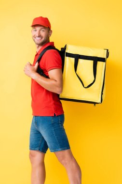 Cheerful delivery man carrying backpack with order on yellow stock vector