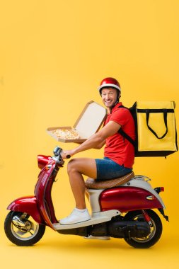 Joyful delivery man with backpack riding red scooter and holding pizza in carton box on yellow stock vector