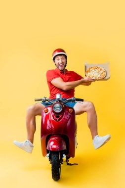 Excited delivery man in helmet riding scooter and holding pizza in carton box on yellow stock vector