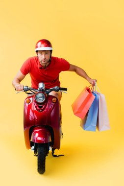 Delivery man in helmet riding scooter and carrying shopping bags on yellow stock vector