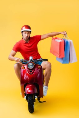 Surprised delivery man in helmet riding scooter and holding shopping bags on yellow stock vector