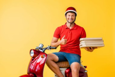 Happy delivery man in helmet holding pizza boxes while showing thumb up near scooter on yellow stock vector